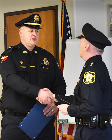 BRYAN EATON/Staff photo. Newburyport Police Lt. Matthew Simons, left, is congratulated by Groveland Police Chief Jeffrey Gillen after receiving a citation. Simons was off duty last month and came across an accident due to a medical condition in which he performed CPR on the victim.