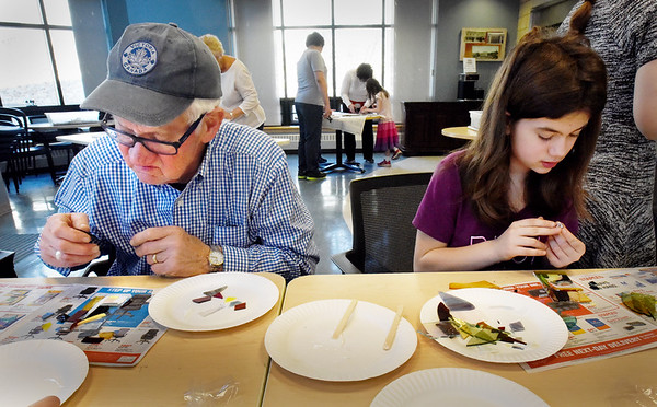 BRYAN EATON/Staff photo. Gunter Sonntag, left, and his granddaughter, Claire Ward, 10, both of Amesbury sort and lay out pieces of glass on Wednesday afternoon. They were at an Intergenerational Mosaic Workshop at the Amesbury Senior Center and co-sponsored by the Children's Room at Amesbury Public Library.
