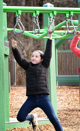 BRYAN EATON/Staff photo. Kellianne Walsh, 12, reaches for the next rung in the monkey bars at the playground at Newbury Elementary School during recess on Monday. The next couple days will be nice for outdoor activities but rain comes in Thursday night into Friday according to weather reports.