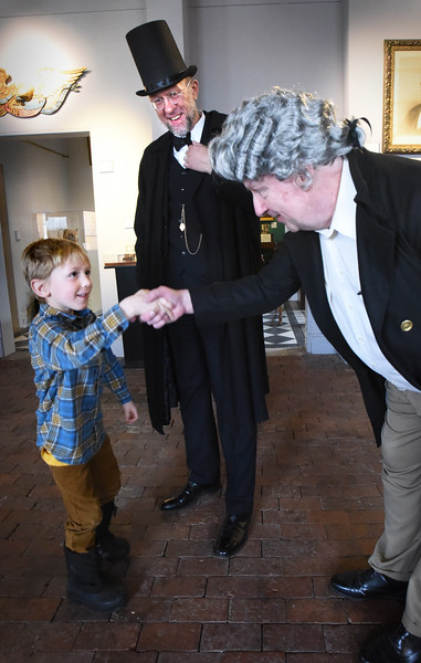 BRYAN EATON/Staff photo. Tate Bishop, 5, of Newburyport gets to meet Abe Lincoln, and George Washington, a.k.a. respectively as Peter Tybinkowski and Paul Armstrong at the Custom House Maritime Museum on Thursday morning. He was there for a scavenger hunt for their Family Fun Days during this week's school vacation.