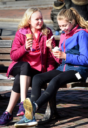 BRYAN EATON/Staff photo. Aby Joyner, left, and Lily LeDuc, both 12, of Newbury enjoy a laugh and some ice cream in Newburyport's Market Square while the sun was out Tuesday afternoon. Today is forecast to be even warmer and could break the record for the warmest day on this date.