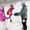 Newburyport: Yesterday's heavy, wet snow was ideal for making snowballs, snowforts and snowmen as these girls were making at the bottom of March's Hill in Newburyport.  From left, Juliana Martin, 11, and Sami Cavanaught, 12, of Newburyport and Grace Montgomery, 12, of Byfield put twigs as arms into their creation as other children, out of school for the day, get in some sledding. Bryan Eaton/Staff Photo