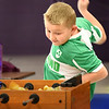 BRYAN EATON/Staff photo. Parker Jovilet, 9, puts all of his wrist power as he twists one of the handles on a foosball table. He was playing a game with Savannah Beauvais, 9, at the Boys and Girls Club which is open for school vacation week.