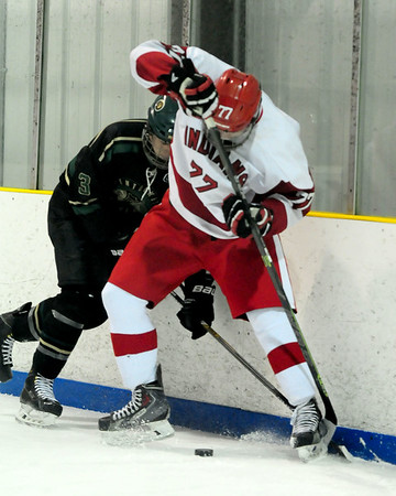 JIM VAIKNORAS/Staff photo Pentucket's  Ben Gardner digs for the puck with Amesbury's Mike Willis at the Valley Forum in Haverhill Saturday night.