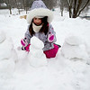 JIM VAIKNORAS/Staff photo Ruby Wilson, 4, of Newburyport, puts the finishing touches on a group of snowmen she made near Marches Hill in Newburyport Saturday morning.The frosty fiques represent her family.