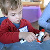 BRYAN EATON/Staff photo.  Sam Mathison, 3, of Maynard puts the mouth on a penguin he made out of round balls on Thursday morning. He was at the Joppa Flats Audubon Education Center, which had different activities for children during school vacation week, with his sister, Callie, 5, and mother, Valerie.