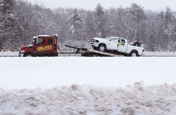 BRYAN EATON/Staff photo. A flatbed truck tows away pickup truck that rolled over the median strip on Interstate 95 northbound in Rowley late Monday morning.