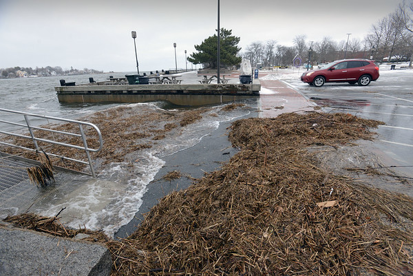 BRYAN EATON/Staff photo. Strong wind and a high tide hit the area before the heavy snow started, the Merrimack River just spilling onto the parking lot at the west of the boardwalk in Newburyport's downtown.