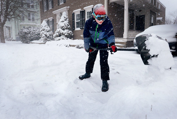BRYAN EATON/Staff photo. Travis Edmunds, 12, clears out in front of his family's Washington Street home in Newburyport as heavy snow started falliing early Thursday afternoon. He was likely back at is as more snow fell into early evening.
