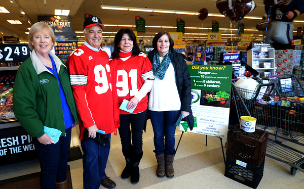 JIM VAIKNORAS/Staff photo Mayor's Ken Gray and Donna Holaday are joined by Ann Gagne and Lynne Corrigan as they collect food for our Neighbor's Table at Stop and Shop in Amesbury Saturday afternoon. Newburyport Mayor Holaday wore a Amesbury High football jersey after losing a bet of the annual Newburyport/Amesbury Thanksgiving day football game won by Amesbury.