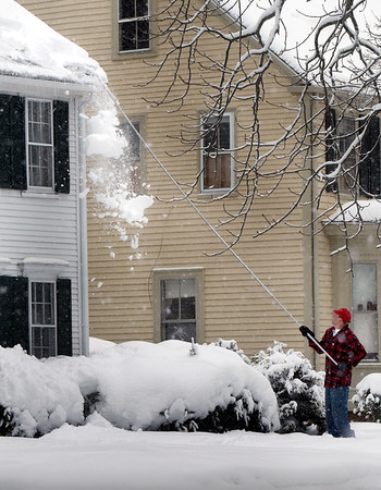 BRYAN EATON/Staff photo. Jim Bailey rakes snow off his home on Main Street at Amesbury's Point Shore on Monday morning. Rain mixed in with the snow during the storm which could potentially stress some buildings