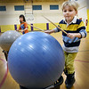 "BRYAN EATON/Staff photo. Grace Jezowski, 10, left, and Henry Maneikis, 5, hop while using drumsticks to bang giant balls at Newbury Elementary School. They were in one of the Explorations programs ""cardio drumming"" led by Maggie Schack which mixes music with excercise for a healthy heart."