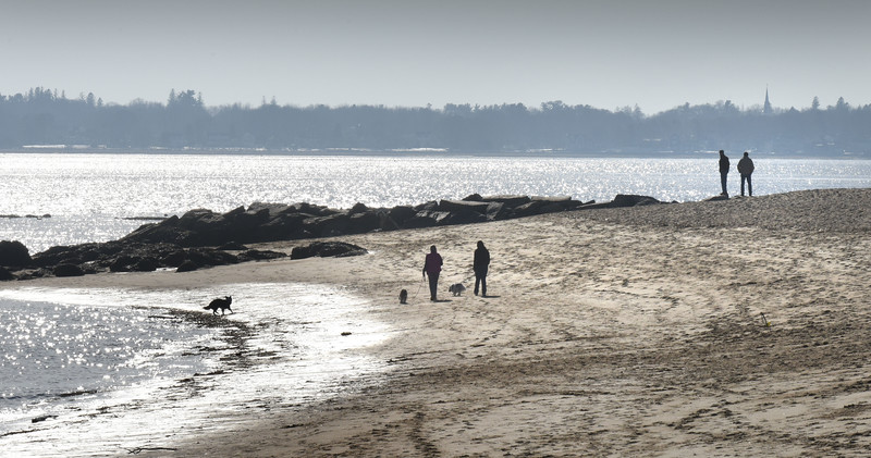 BRYAN EATON/Staff photo.  People and their dogs are silhouetted by a bright sun reflecting off the Merrimack River at Salisbury Beach State Reservation on Wednesday. The temperature for Thursday is to be in the 60's with nicer weather still for the weekend, though rain possible late Saturday afternoon and evening.