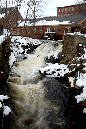 JIM VAIKNORAS/Staff photo  The Powow River , swelled by melting snow, rushes through the Upper Millyard in Amesbury Sunday morning.
