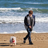 JIM VAIKNORAS/Staff photo Ryan Kiley of Merrimac , enjoys the unseasonably warm weather as he walks with his dog Rocky on Salisbury Beach Monday afternoon. Mild weather is forecasted to continue this week with tempuratures to reach 60 by Friday.