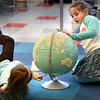 BRYAN EATON/Staff photo. Piper Doherty, 7, left, and Grace Andron, 6, pick out places on the globe in Sue Harrington's second grade class at Bresnahan School in Newburyport on Wednesday afternoon. They were learning about geography and finding places on the globe that they learned from in an atlas.