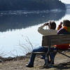 BRYAN EATON/Staff photo. Margaret Newsome, left, and Janet Robinson sit in the sun on a bench at Alliance Park in Amesbury on Thursday morning. The two, from Ipswich, were scoping the Merrimack River for bald eagles.