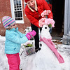BRYAN EATON/Staff photo. Isabella Veno, 4, helps her mom, Amy McLaughlin put together a Valentine-themed snowman in front of her Liberty Street shop in Newburyport, Amy McLaughlin Lifestyles.
