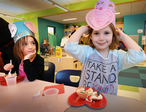 "BRYAN EATON/Staff photo. Molly Mosquera, left, and Teigan LaFrance, both 5, wear Valentine hats while eating ""friendship Sundaes"" made of waffle cone bowls, yogurt and fresh fruit. They were at a Valentine's Day party in Giavanna Foster's pre-K class at the Bresnahan School in Newburyport."