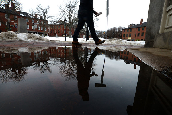 JIM VAIKNORAS/Staff photo A mon walking down State Street in Newburyport is reflected in a large puddle on Liberty Street Erley Sunday morning. Warm weather predicted this week should melt most snow and make more puddles.