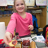 JIM VAIKNORAS/Staff photo Brooke Baumann serves jam and maple syrup to celebrate her Canadian heritage at the Salisbury Elementary School 2nd grade Passport to Learning Friday afternoon. Each 2nd grader at the school made a display and gave a short presentation about their ethnic heritage.