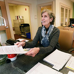 BRYAN EATON/Staff photo. Meg De Give volunteers at front desk of the Newburyport Senior Center to get tax credits.