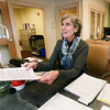 BRYAN EATON/Staff photo. Meg De Give volunteers at front desk of the Newburyport Senior Center to get tax credits.