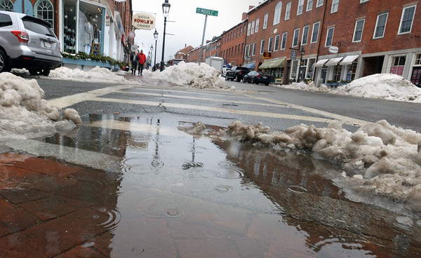 BRYAN EATON/Staff photo. Melting snow created puddles in downtown Newburyport on State at Middle Streets on Wednesday. Rain was forecast overnight then turning to snow with warm weather for the weekend.