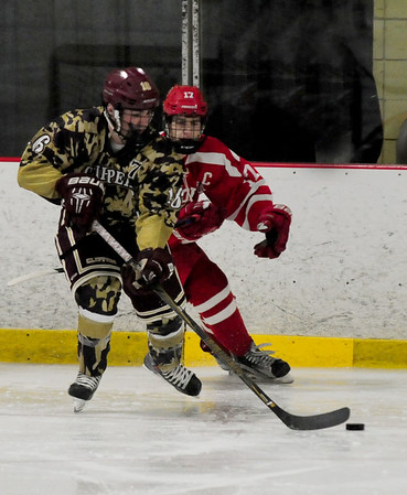 JIM VAIKNORAS/Staff photo Newburyport's Matthew Donlan races for the puck with St John's Tyler Reynolds during the Newburyport Five Cent Savings Bank Tournament at the Graf Rink in Newburyport Friday night.