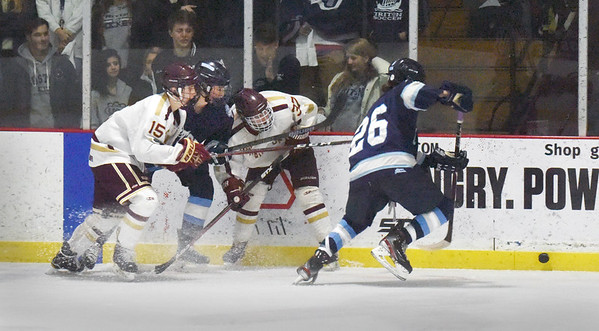 BRYAN EATON/Staff photo. Triton's Jack Forrest gets the puck away from a jam up on the boards.