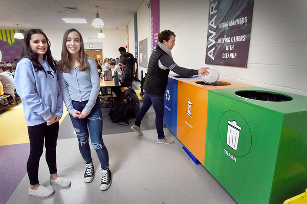 BRYAN EATON/Staff Photo. Nock Middle School staffer Jamee Buchmayr, right, puts food waste into a composting bin aside trash and recyling bins that Lexi Klapes and Gianna Minichiello painted in the cafeteria.