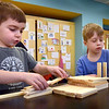 BRYAN EATON/Staff Photo. Oliver Muzerall, 5, left, and Quint Caldwell, 6, work on a model of a fishing dock in Kristen Spinney's STEM class at the Bresnahan School in Newburyport. They were using Keva wood planks to use their creativity and engineering skills to create different structures.