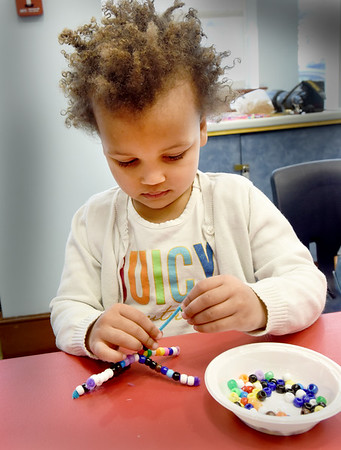 BRYAN EATON/Staff Photo. Norah Boateng, 3, of Newburyport uses pipe cleaners and pony beads to make colorful and decorative snowflakes. She was in craft time in the Children's Room at the Newburyport Public Library.