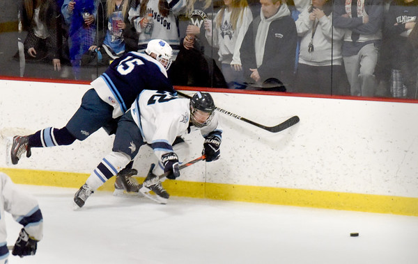 BRYAN EATON/Staff photo. A Wilmington players slams into Tyler Godfrey trying to send the puck into Triton ice.