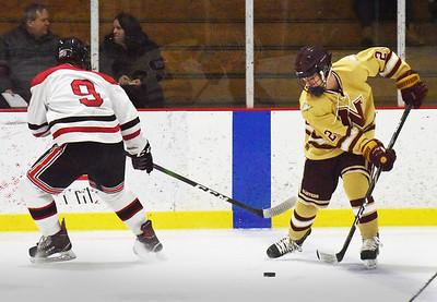 BRYAN EATON/Staff photo. Zachary Wilson maneuvers the puck around Winchester forward Ryan McCarthy.