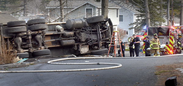 BRYAN EATON/Staff Photo. Amesbury firefighters worked to free the driver of this Mello Disposal truck which tipped over on Lake Shore Drive in Amesbury on Wednesday morning.