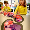 BRYAN EATON/Staff Photo. Micah Schulman, 4, left, and Juliet Swift, 5, glue crepe paper squares into the shape of a heart as Valentine's Day is just around the corner. The pre-kindergartners in Tanasi Fahey's class at the Bresnahan School were making the window-cling hearts to take home.