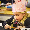 BRYAN EATON/Staff Photo. Dannie Sheehan, 5, does scratch art at Amesbury Elementary School where they color a piece of paper with different shades, let it dry, then paint it black to scratch away and make a design, in this a photo of home complete with dog. The kindergartners were wearing crowns they made to celebrate the 100th day of school on Tuesday.