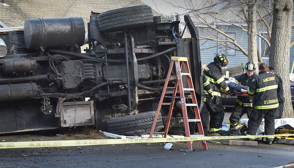 BRYAN EATON/Staff Photo. Amesbury firefighters remove the driver of this Mello Disposal truck which tipped over on Lake Shore Drive in Amesbury on Wednesday morning.