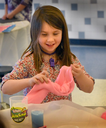 BRYAN EATON/Staff Photo. Keira Dower, 6, has fun with Mega Flarp Noise Putty creating different shapes with the slimy putty. When the youngsters put the material back into the can it makes different noises eliciting giggles from them.