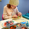 BRYAN EATON/Staff Photo. Kara Logan, 10, wraps a strand off gummy candy around Rice Krispie blocks as she and her brother Daniel, 7, make candy sushi. They were at the Amesbury Public Library making the non-seafood confections provided by the Friends of the Amesbury Public Library.