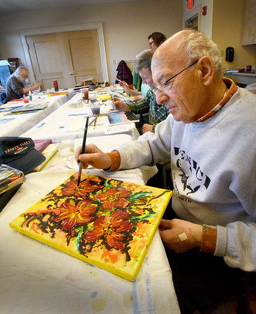 BRYAN EATON/Staff Photo. Walter Maziarski of Newburyport, who took up painting 20 years ago, creates a colorful array of lillies. He was in the painting group which meets on Thursdays at the Newburyport Senior and Community Center with about ten other artists.