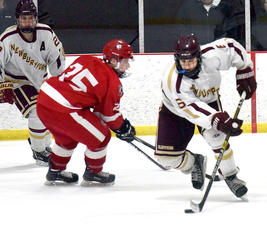 BRYAN EATON/Staff photo. Jonathan Groth gets the puck away from Amesbury's Ethan Lintner.