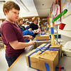 BRYAN EATON/Staff Photo. Dominick Bagley, 9, uses a syringe attached to tubing filled with water creating a hydraulic aparatus to life a crane hoisting a cup of water. He was in the Explorations afterschool program for STEM Robotics which meets on Tuesdays.