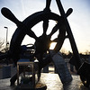 BRYAN EATON/Staff Photo. A stronger sun silhouettes the wheel of the Fisherman's Memorial on the Newburyport waterfront Monday afternoon. The weather of late has been spring-like, indeed real spring is in 23 days.