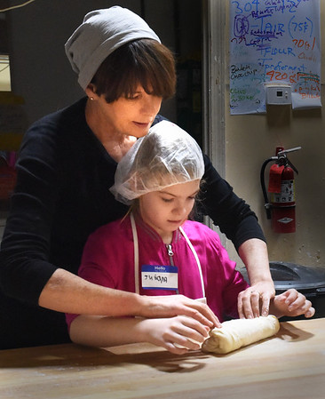 BRYAN EATON/Staff Photo. Jane Kenny works with Juliana Lewis, 8, as she start to roll her baguette.