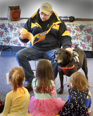 BRYAN EATON/Staff Photo. Don Jarvis reads his book Mocha: The Superhero Service Dog to about 40 youngsters and adults at the Newbury Public Library. The books tells what it's like to be a service dog from the canine's perspective.