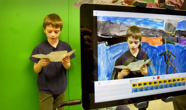 BRYAN EATON/Staff Photo. Hunter Gauthier, 8, reads his research in front of a green screen while being videotaped superimposed over his painting at Bruce McBrien's technology class at Amesbury Elementary School. The project culminated the third-graders' study of owls and their habitats where they presented their findings with their artwork in the video directed by fellow student Ryan John Downer, Jr.