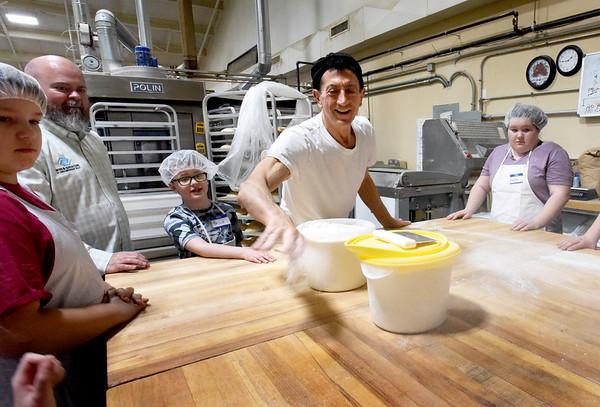 BRYAN EATON/Staff Photo. Malatesta throws flour onto the work surface.