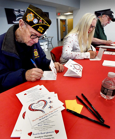 BRYAN EATON/Staff Photo. U.S. Navy veteran Henry Cross of Merrimac, left, Karen Cook of Amesbury, and Vietnam-era U.S. Army veteran Dudley Farquhar of Merrimac, were three of several dozen volunteers including area police, fire and community members who were signing Valentine cards at the Heart To Heart event at Amesbury Chevrolet, one of the sponsors as well as Coastal Connections. Area school children also filled out cards that will go to about 3,000 veterans in the seven VA hospitals in Massachusetts and nursing homes and those in their own homes. Special thanks went to the Sgt. Jordan M. Shay Memorial Foundation, Loral Press, Inc. and the volunteers who made the event successful.